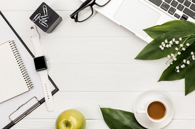 Materiały piśmienne z laptopem i śniadaniem na białym drewnianym biurku