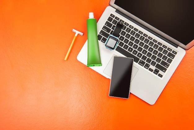 Materiały podróżnicze, takie jak laptop, smartwatch, telefon komórkowy, żółta golarka i pasta do zębów