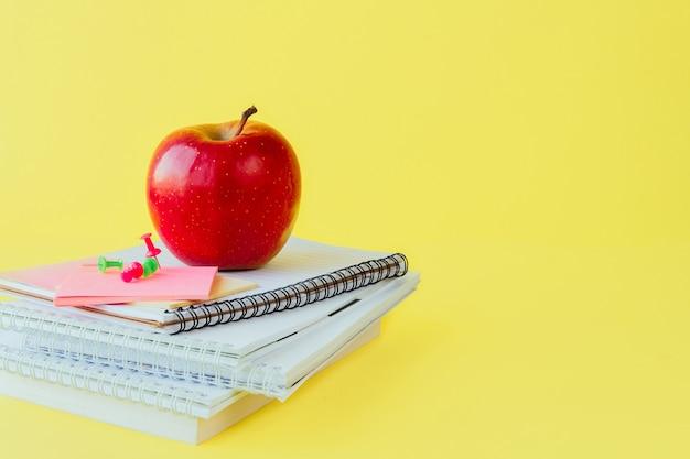 Materiały szkolne i biurowe na stole w klasie na żółtym tle