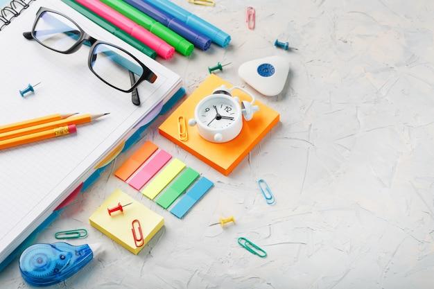 Materiały szkolne leżą na szarej fakturze z wolną przestrzenią.