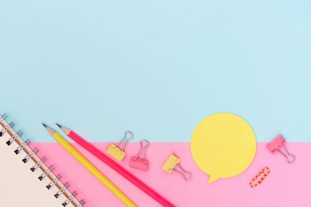 Materiały szkolne na różowym i niebieskim tle. kreatywny powrót do szkoły