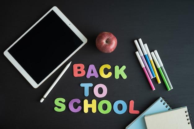 Materiały szkolne z napisem back to school na czarnym tle.