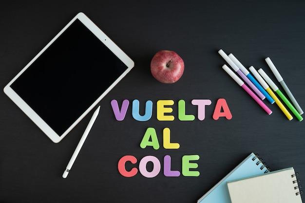 Materiały szkolne z napisem regreso a classe w języku hiszpańskim na czarnym tle.