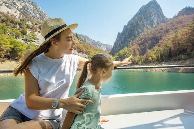 Mather z małą córeczką na statku wycieczkowym lub łodzi, ciesząc się jeziorem na letnie wakacje. koncepcja wakacje podróży i wycieczek.