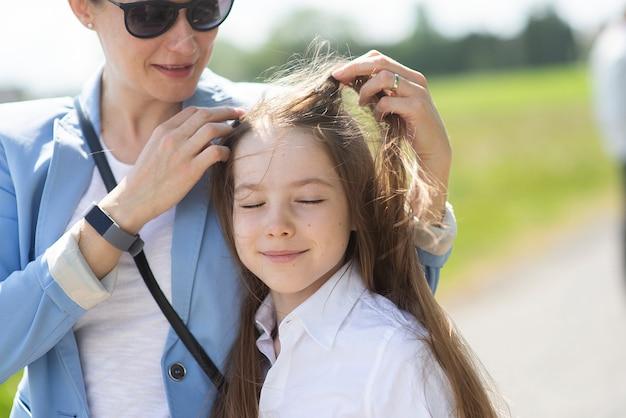 Matka bawi się długimi włosami córki w wietrzny dzień