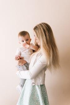 Matka bawi się z chłopcem, szczęśliwa rodzina dobrze bawi się w pomieszczeniu, wesoły słodki portret dziecka, mama i dziecko, zdrowy maluch, podnoszenie rzucania, prowadzenie gry