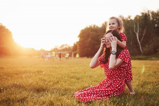 Matka bawi się z córką na ulicy w parku o zachodzie słońca