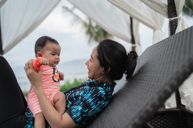 Matka bawi się z dzieckiem siedzącym na kolanach, gdy leży