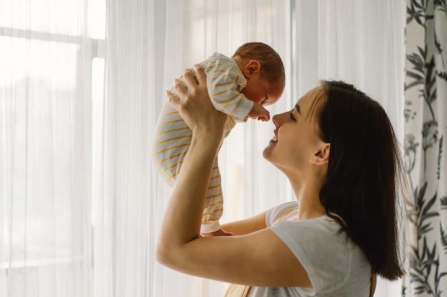 Matka bawi się z synem noworodka w domu w pobliżu okna. szczęśliwe niemowlę i mama.