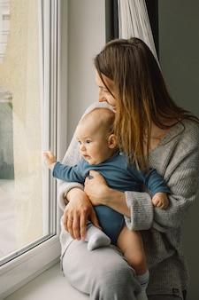Matka bawi się z synkiem w domu przy oknie. szczęśliwe niemowlę i mama.