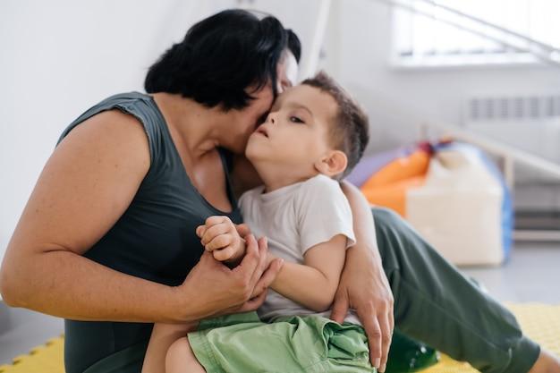 Matka bawi się z uroczym niepełnosprawnym dzieckiem mózgowym porażeniem dziecięcym