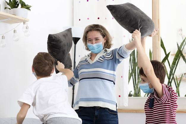 Matka bawi się ze swoimi dziećmi w domu podczas noszenia masek medycznych