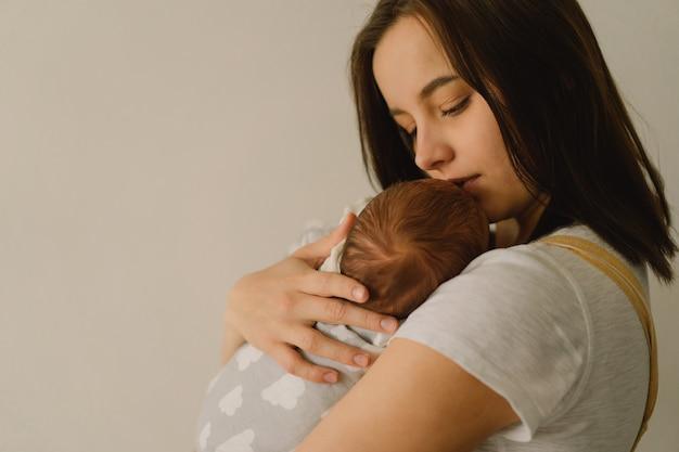 Matka bawić się z synem nowonarodzonego dziecka w domu. szczęśliwe niemowlę i mama.