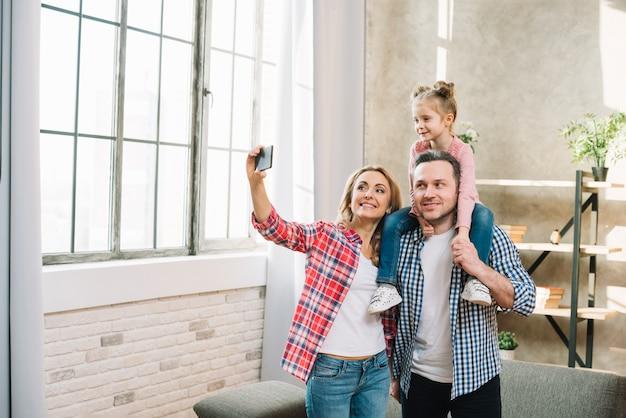 Matka bierze selfie na telefonie komórkowym z jej córką i mężem