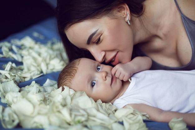 Matka brunetka z nowonarodzonym chłopcem leży na łóżku z białymi płatkami róż