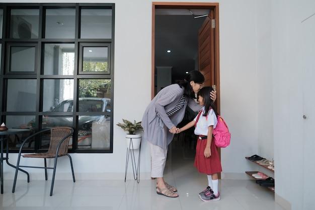 Matka całuje córkę w czoło przed zabraniem jej do szkoły