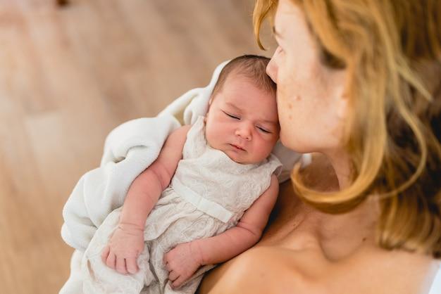 Matka całuje jej nowonarodzoną córkę po karmieniu piersią