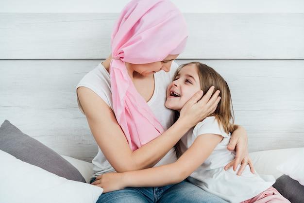 Matka chora na raka nosi różową chustkę na głowie, obejmującą i pieszczącą twarz córki pięknymi blond włosami. oboje siedzą szczęśliwie w łóżku na białym tle