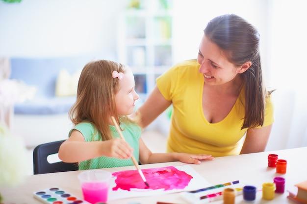 Matka córka maluje akwarelę na kartce papieru, siedząc w domu przy stole w jasnym pokoju.
