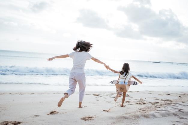 Matka córka trzyma rękę i biegnie z kartonowym samolotem