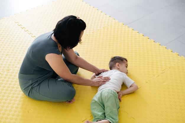 Matka ćwicząca ćwiczenia fizyczne bawiąca się z niepełnosprawnym chłopcem