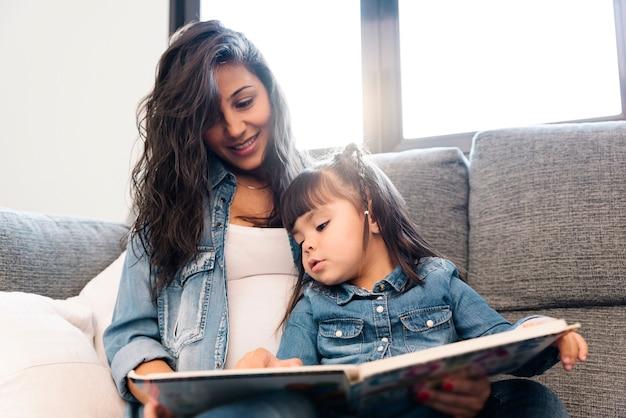 Matka czyta książkę córce w domu.