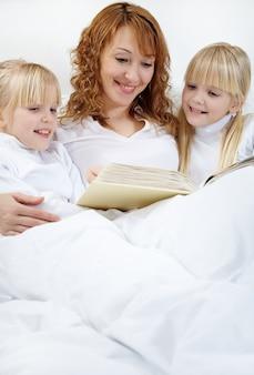 Matka czytania jej córki w łóżku