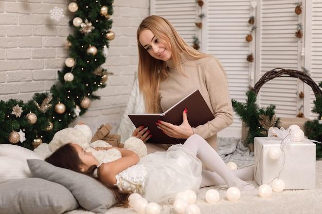 Matka czytanie książki do swojej córeczki w pobliżu choinki w domu