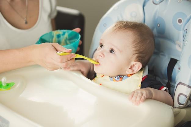 Matka daje chłopcu owsiankę z plastikowej łyżki
