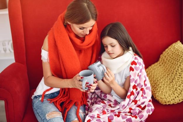 Matka daje swojej chorej córce gorącą herbatę