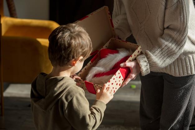 Matka daje synowi prezent z czapką świętego mikołaja