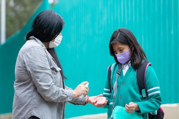 Matka dezynfekuje córkę przed wejściem do szkoły