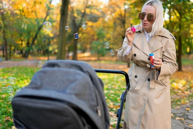 Matka dmucha bańkami mydlanymi, aby zabawiać dziecko w wózku