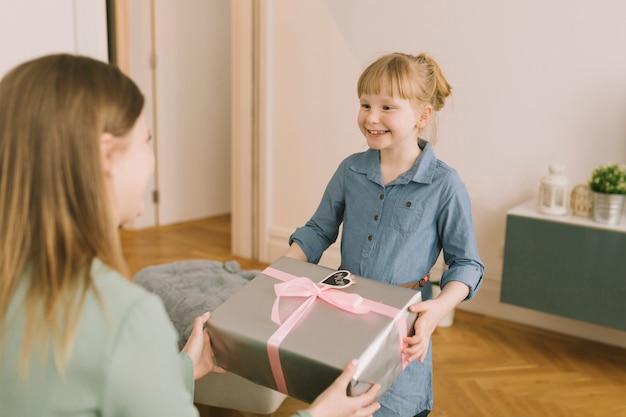 Matka dnia pojęcie z dzieciakiem daje prezenta pudełku