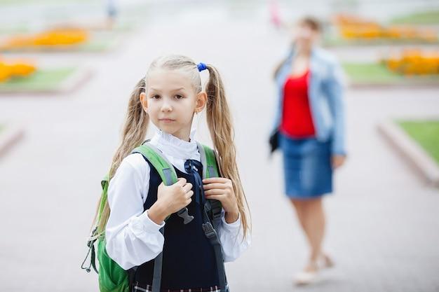 Matka eskortuje uczennicę do szkoły z kucykami i torbą. selektywne skupienie się na dziewczynie.