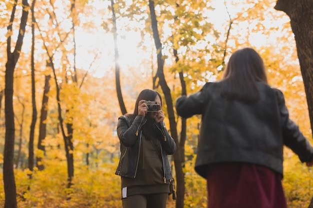 Matka fotograf robi zdjęcia swojej córce jesienią w parku. hobby, sztuka fotograficzna i koncepcja rekreacji.