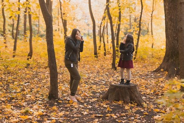 Matka fotograf robi zdjęcia swojej córce w parku w jesienne hobby fotoarty i