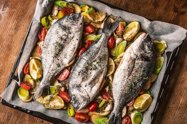 Matka gotuje obiad dla całej rodziny, piecze ryby dorado