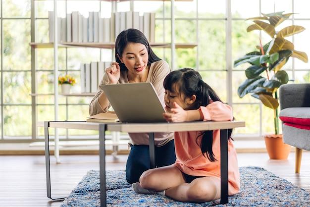 Matka i azjatyckie dziecko mała dziewczynka ucząca się i patrząc na laptop, odrabiająca pracę domową, studiująca wiedzę z systemem e-learningu edukacji online. wideokonferencja dla dzieci z nauczycielem korepetytorem w domu