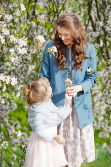 Matka i córeczka spaceru w kwitnącym ogrodzie jabłkowym. mama kocha swoje dziecko. wiosenna historia. szczęśliwa rodzina w piękny wiosenny dzień
