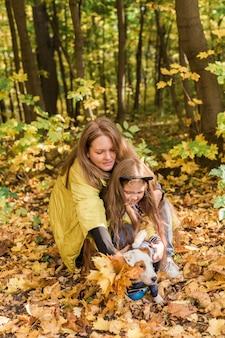 Matka i córeczka spaceru z psem jack russell terrier w jesiennej pogodzie. stylowa córeczka i jej matka. szczęśliwe dzieciństwo. na zewnątrz portret szczęśliwej rodziny.