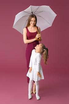 Matka i córeczka z parasolem na kolorowym tle