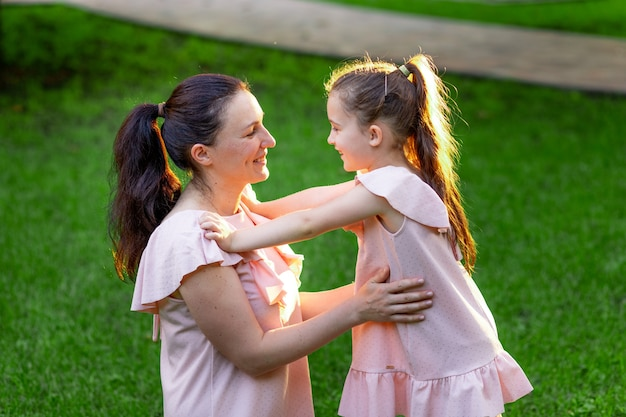Matka i córka 5-6 lat spacerujące po parku latem, córka i mama śmiejąca się na ławce, koncepcja szczęśliwej rodziny, związek matki z dzieckiem, dzień matki