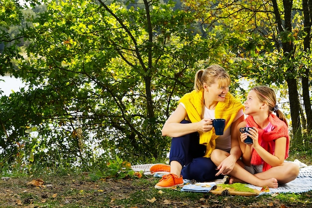 Matka i córka bawią się na kocu w jesiennym lesie w pobliżu rzeki lub jeziora. młoda matka bawi się z córką w jesienny park w słoneczny dzień