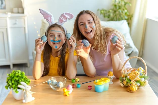 Matka i córka bawią się pisankami. szczęśliwa rodzina przygotowuje się do wielkanocy. cute little girl dziecko sobie uszy królika.