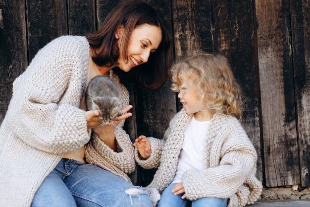Matka i córka bawią się z małym kotkiem przy drewnianej ścianie.