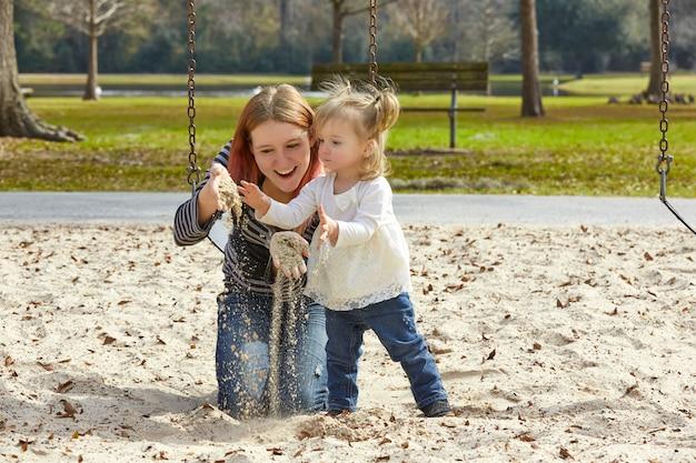 Matka i córka bawić się z piaskiem w parku