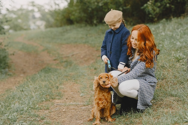 Matka i córka bawić się z psem. rodzina w parku jesień. koncepcja zwierząt domowych, zwierząt domowych i stylu życia. jesienny czas.