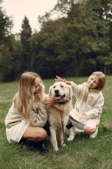 Matka i córka bawić się z psem. rodzina w parku jesień. koncepcja zwierząt domowych, zwierząt domowych i stylu życia