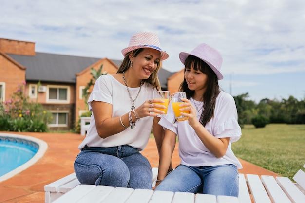 Matka i córka ciesząc się dzień picia soku pomarańczowego.